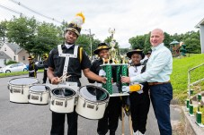 WATERBURY, CT. 20 August 2018-082018 - Berkeley Knight team members from left, Drummer Darren Richards, Drill team members Carrizma Gore and Tahanya Hillard present their World Championship trophy to Waterbury YMCA CEO Jim O'Rourke in the parking lot of the Berkeley City Recreation Center in Waterbury on Monday evening. Bill Shettle Republican-American