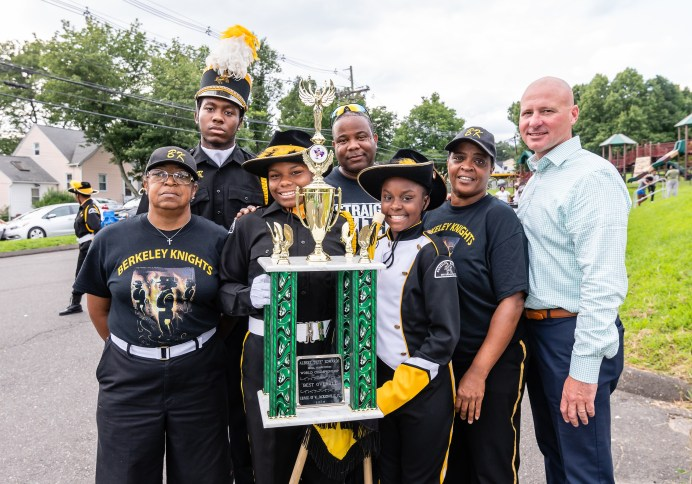 WATERBURY, CT. 20 August 2018-082018 - From left, Berkeley Knight members and staff Dorothy Knight, Darren Richards, Carrizma Gore, Drill Master Mike Tripp, Tahanya Hillard, Natalie Brockett, and YMCA CEO Jim O'Rourke stand together with the World Championship Trophy they won at the World Championship Drill Competition in Jacksonville, FL, at the Berkeley City Recreation Center in Waterbury on Monday evening. Bill Shettle Republican-American