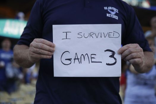 A fan holds up a sign Oct. 27, the day the 18-inning Game 3 of the World Series between the Los Angeles Dodgers and Boston Red Sox ended in Los Angeles. The sign was spotted before Game 4 began later that day. (AP Photo/Jae C. Hong)