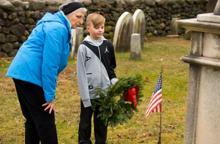 WATERTOWN, CT-121518JS10- Katie Gabrielson, with the Trumbull-Porter Chapter of the Daughters of the American Revolution, left, talks with Jame Young, 9, of Bethlehem, a member of the Bethlehem Elementary student council, as he prepares to lay a wreath at the base of the headstone of General Garrit B. Smith, who fought in the War of 1812, during the annual Wreaths Across America ceremony held Saturday at the Old Burying Ground in Watertown. The event was hosted by the Trumbull-Porter Chapter of the Daughters of the American Revolution and the Waterbury Veterans Memorial Committee. Jim Shannon Republican American