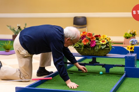 WOODBURY, CT. 15 February 2019-021519 - Bob Taylor, President of the Community Services Council of Woodbury tries to retrieve his ball after he failed to get the ball by the turning obstacle as he plays the indoor mini-golf course at the Senior Center in Woodbury on Friday. This is a very tough hole for Bob as he has failed for the last couple of years to get the ball by the obstacle. Bill Shettle Republican-American