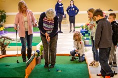 WOODBURY, CT. 15 February 2019-021519 - From right center, Autumn Shugrue, 6, kneeling, Brynn Clampett, 10, Elliott Shugrue, 9, Gavin Clampett, 7, and Betsy Daniels, left, all look on intently as great grandma Elizabeth Barry taps a putt in on the fourth hole, as they play the indoor mini-golf course at the Senior Center in Woodbury on Friday. Bill Shettle Republican-American