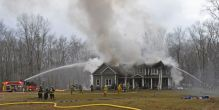 Firefighters from Northville and Kent fire departments spray water on a fire Sunday afternoon that badly damaged the home of Marika and Kim Coolbeth at 17 Tamshell Drive in the Kent Hollow section of town. The family was not home at the time the fire began, but arrived home to find the flames spreading. Lynn Mellis Worthington Republican-American
