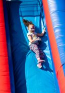 NAUGATUCK, CT. 18 May 2019-051819 - Violet Schiano, 9, of Ansonia slides down the big inflatable slide, during the annual Ion Bank/Naugatuck Spring Festival on Church Street in Naugatuck on Saturday. Bill Shettle Republican-American