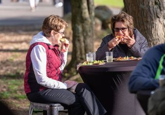 Libby D'orso, left, and Sue McGrath, both of Waterbury, enjoy a slice of pizza during the Greater Waterbury Campership Fund's Big Green Truck party at Camp Mataucha in Watertown on Thursday. Bill Shettle Republican-American