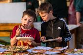 Connor Ball, 9, of Woodbury, left, eats his pizza at the table, as Griffin Bradshaw, 9, of Watertown, decides what kind of pizza to have during the Greater Waterbury Campership Fund's Big Green Truck party at Camp Mataucha in Watertown on Thursday. Bill Shettle Republican-American