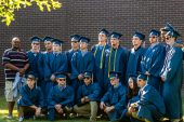 Oxford High School football defensive coordinator Joshua Harris, left, stands for a group photo with his graduating players, before the commencement ceremonies at Oxford High School on June 11, 2019. Bill Shettle/Republican-American