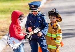 """SOUTHBURY, CT. 26 October 2019-102619BS376 - Officer Lucy Shah, 6, center, checks out Lucas Kercado (dressed as Miguel from Coco""""), 4, guitar, as her brother Fireman Henry Shah, 3, looks on, during the ninth Annual Trick-or-Treat Spooktacular at the Southbury Center Firehouse on Saturday. The firehouse was transformed into a maze of different themed-rooms where kids could collect treats. Bill Shettle Republican-American"""