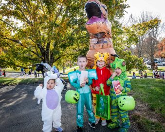 SOUTHBURY, CT. 26 October 2019-102619BS382 - From left, Norah Gonzalez, 2, her brother Elijah, 6, their friend Anthony Correa, 6, and Norah's other brother Elan, 4, stand with a T-Rex for a photo, during the ninth Annual Trick-or-Treat Spooktacular at the Southbury Center Firehouse on Saturday. Bill Shettle Republican-American