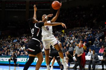 Connecticut's Crystal Dangerfield, right, shoots over Cincinnati's Antoinette Miller in the first half of an NCAA college basketball game, Thursday, Jan. 30, 2020, in Storrs, Conn. (AP Photo/Jessica Hill)
