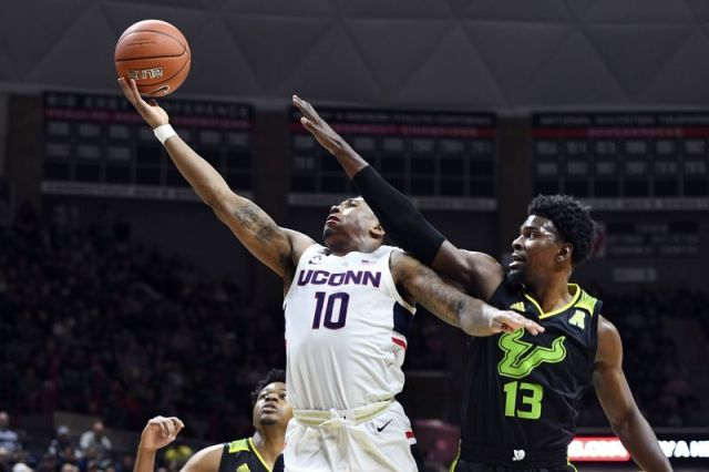 Connecticut's Brendan Adams (10) shoots over South Florida's Justin Brown (13) during the first half of an NCAA college basketball game Sunday, Feb. 23, 2020, in Storrs, Conn. (AP Photo/Stephen Dunn)