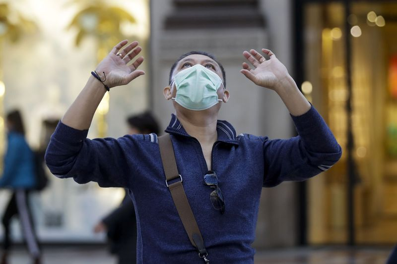 A man wearing a protective mask looks up as he walks along the Vittorio Emanuele Gallery shopping arcade, in Milan, Italy, Friday, Feb. 28, 2020. Authorities have decided to re-open schools and museums in some of the less areas less hard-hit by the coronavirus outbreak, in which Italy has the most cases outside of Asia. (AP Photo/Luca Bruno)