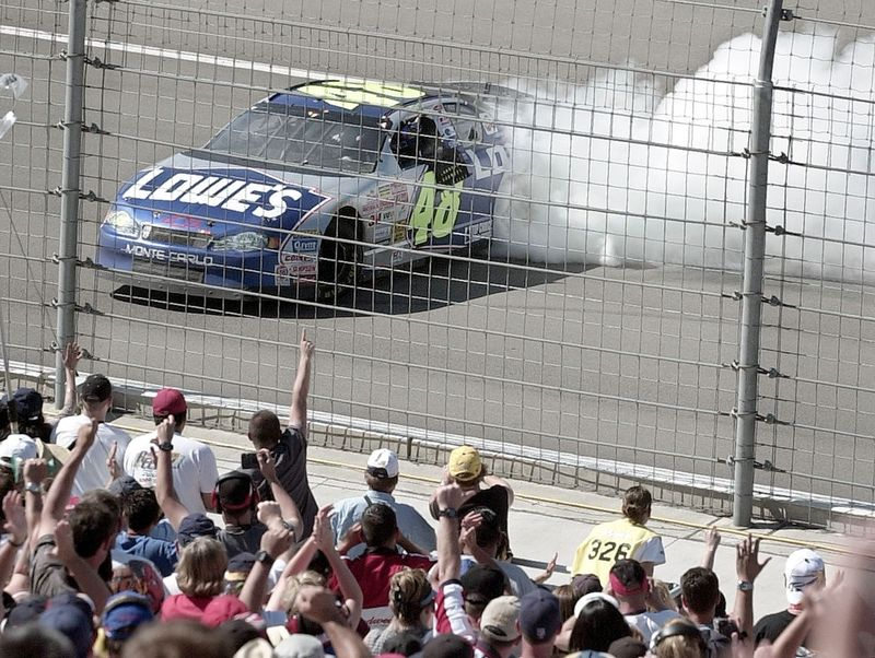 FILE - In this April 28, 2002, file photo, Jimmie Johnson does a burnout in front of fans afer winning NASCAR auto race at California Speedway in Fontana, Calif. When Johnson won his first NASCAR Cup Series race at Fontana 18 years ago, this famously worn-out asphalt track had a whole lot less wear and tear. So did Johnson, who is visiting his home track this weekend for the last time as a full-time driver. (AP Photo/Mark J. Terrill, File)