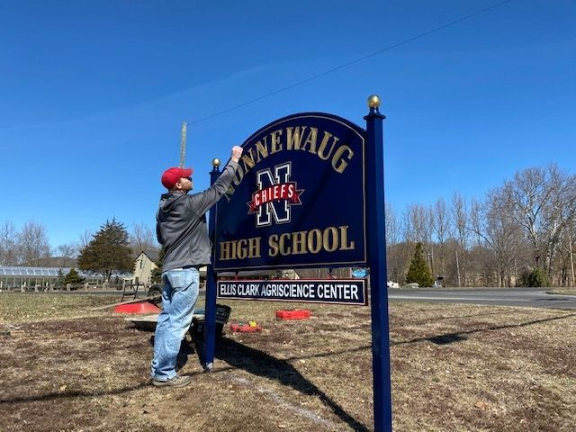 WOODBURY -- Bob Neth, Jr., of Connecticut Signcraft of Naugatuck, touches up the new sign for Nonnewaug High School at the corner of Route 6 and Middle Road Turnpike in Woodbury on Monday. Nonnewaug and all state schools remain closed.Contributed