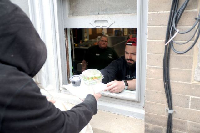 Bruno Matarazzo Jr. Republican-AmericanA client receives a meal from Sean Cote through the basement window of Community Soup Kitchen in Torrington on Wednesday to help limit the spread of the coronavirus.