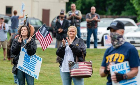 Jennifer DiDomizio and Debbie Toomey, both of Waterbury and members of the Rat Pack Motorcycle Club, applaud one of the speakers during a rally to support local and national law enforcement Saturday at Seth Thomas Park in Thomaston. Jim Shannon Republican-American