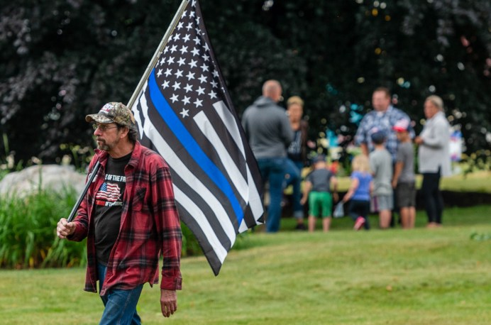 Al Pfaefflin of Thomaston, walks with a Thin Blue Line flag during a rally to support local and national law enforcement Saturday at Seth Thomas Park in Thomaston. Jim Shannon Republican-American