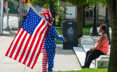Francisco Ramos of Waterbury dressed for the 4th of July holiday, talks with a resident in front of Waterbury City Hall on Saturday. Ramos came down to city hall after he heard about the vandalism of the Christopher Columbus statue. Jim Shannon Republican-American