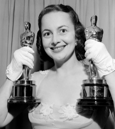 Olivia de Havilland holds her two Oscars as she returns home following the Academy Awards presentations in 1950, having won her second. (Associated Press)