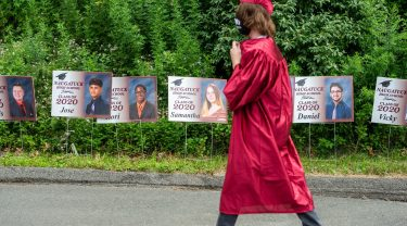 A Naugatuck High School graduate walks past sigs of fellow graduates as they make their way to graduation ceremonies Friday at Naugatuck High School. The school held five separate ceremonies with about 40 graduates at each due to limitations on gatherings. Jim Shannon Republican-American