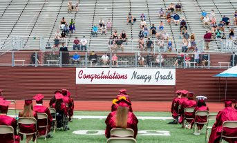 Naugatuck High School graduates listen to Principal John Harris during graduation ceremonies Friday at Naugatuck High School. The school held five separate ceremonies with about 40 graduates at each due to limitations on gatherings. Jim Shannon Republican-American