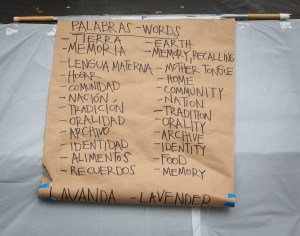 A poster with a list of words in English and Spanish used to evoke memories. In the Spanish column the list contains Tierra, Memoria, Lengua materna, Hogar, Comunidad, Nación, Tradición, Oralidad, Archivo, Identidad, Alimentos, and Recuerdos. In the English column the list includes Earth, Memory, Recalling, Mother tongue, Home, Community, Nation, Tradition, Orality, Archive, Identity, Food, and Memory. At the bottom of the poster, in a bigger font, there are the words Lavanda and Lavender, each one aligned with its respective column. Photo by Cinthya Santos-Briones for Brewing Memories workshop, October 24, 2020.
