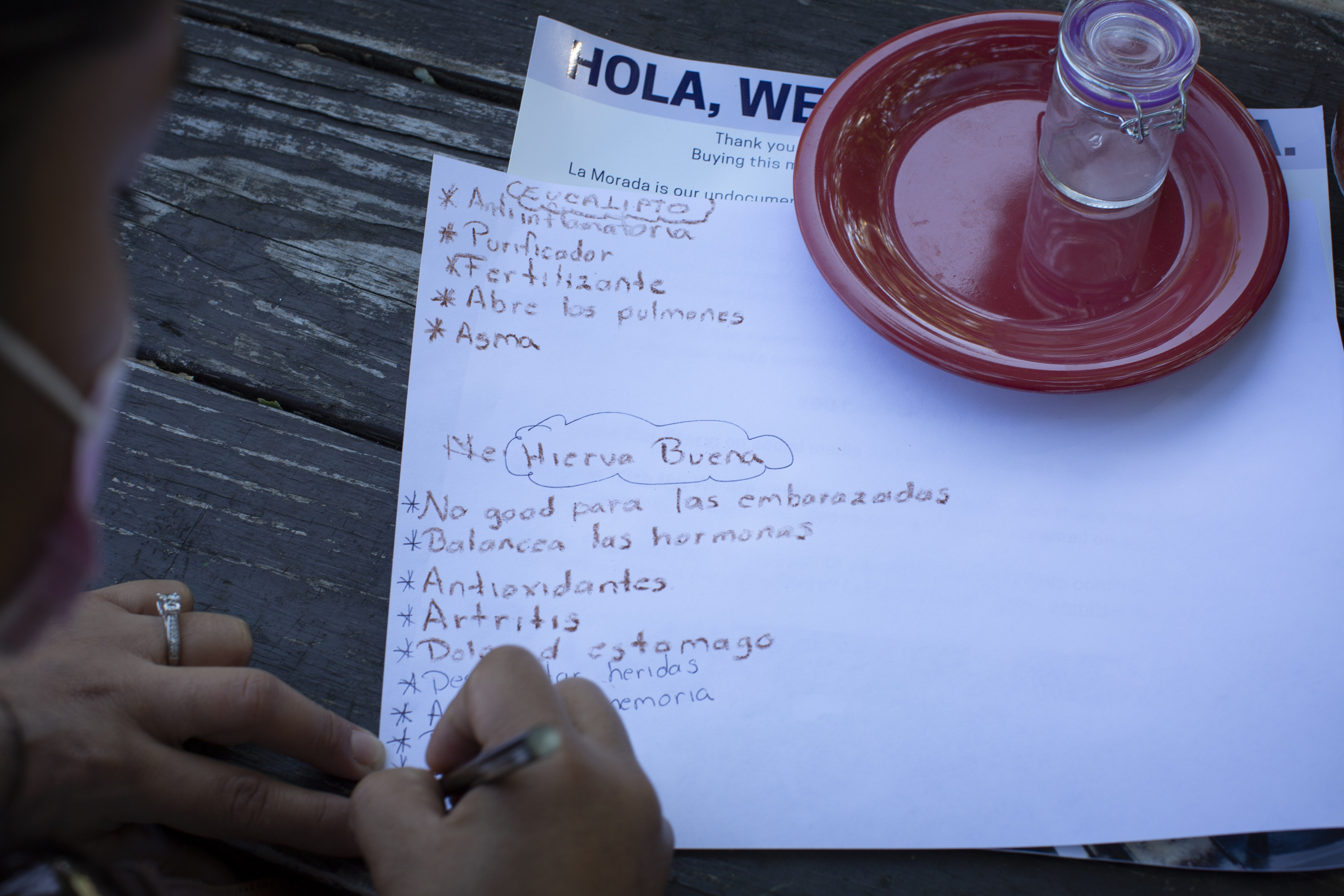 An over-the-shoulder view of a participant with a pink mask taking notes in Spanish about the properties and uses of eucalyptus and spearmint. In the background, on a wooden table, there is a red plastic plate with a glass jar on it. Underneath the piece of paper in which the participant is writing there is a flyer with information about La morada restaurant and its activities during the Covid-19 pandemic. Photo by Cinthya Santos-Briones for Brewing Memories workshop, October 3, 2020.