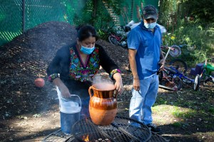 Natalia, who is wearing an Indigenous Mexican embroidered shirt (Black with flowers) and a long denim skirt, puts hot water on a big pot made out of clay that stands on top of the fire; Antonio, who is wearing a light blue shirt, jeans, a baseball cap, stands nearby watching the operation. Both are wearing medical masks. Smoke comes out of the fire. The mounds of soil in the background reflect the morning sunlight.
