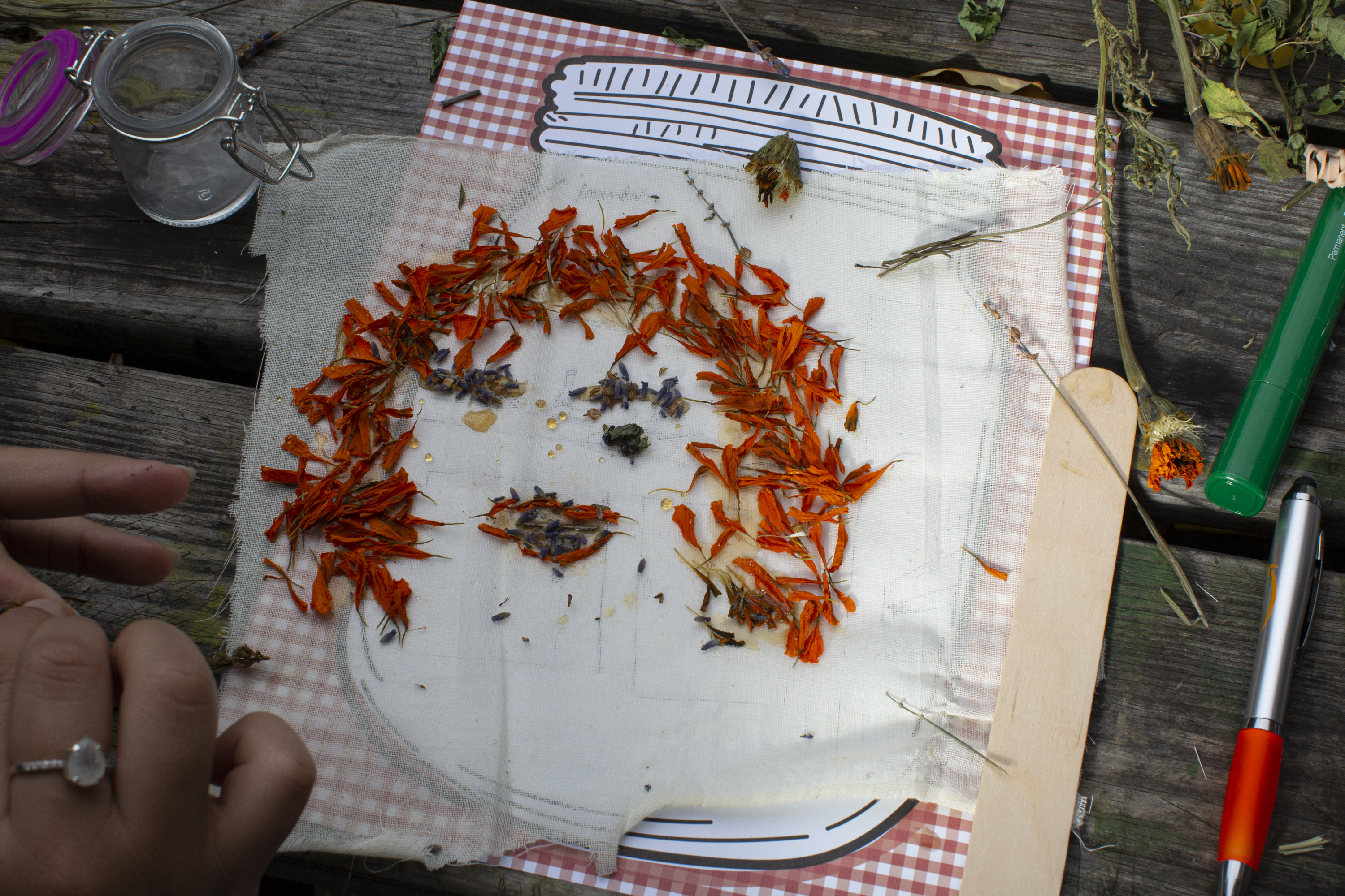 A drawing in the shape of a human face made out of honey and dry herbs (Marigold dried petals and Lavender). Photo by Cinthya Santos-Briones for Brewing Memories workshop, October 24, 2020.