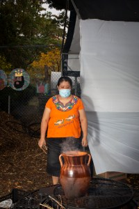 Natalia, wearing an Indigenous Mexican embroidered shirt (orange with flowers), a long black skirt, and medical mask, stands near the fire. A big pot made out of clay that stands on top of the fire. Photo by Cinthya Santos-Briones for Brewing Memories workshop, October 24, 2020.