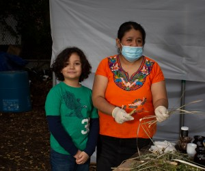 Natalia, wearing an Indigenous Mexican embroidered shirt (orange with flowers), a long black skirt, medical mask and surgical gloves, cuts dried branches of lemongrass. A young workshop participant, wearing a green shirt over a long sleeve black shirt, smiles to the camera. Photo by Cinthya Santos-Briones for Brewing Memories workshop, October 24, 2020.