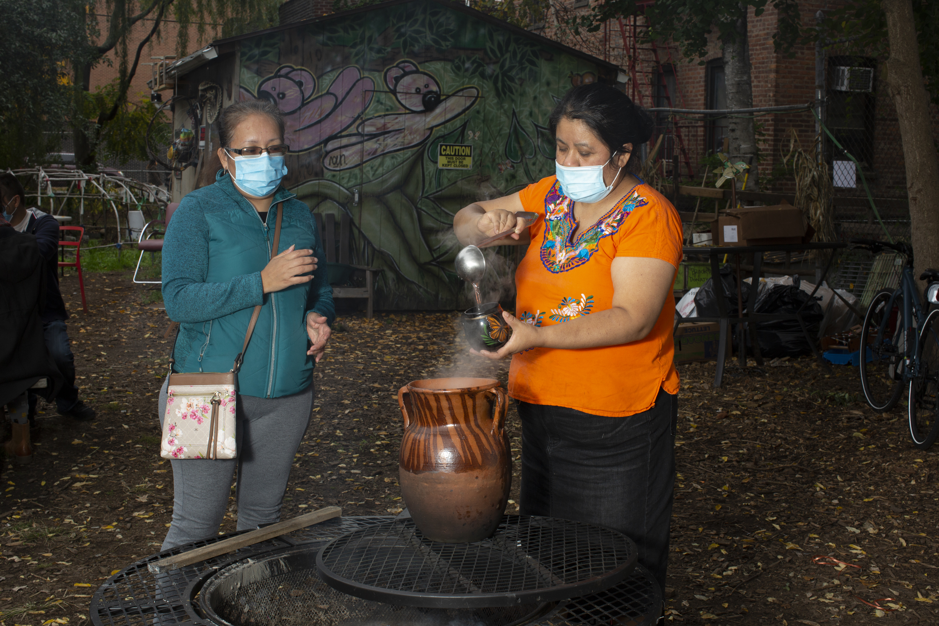 Natalia, wearing an Indigenous Mexican embroidered shirt (orange with flowers), a long black skirt, stands near a fire, serving tea to a workshop participant who is wearing a green jacket and grey pants. Both wear medical masks. Photo by Cinthya Santos-Briones for Brewing Memories workshop, October 24, 2020.