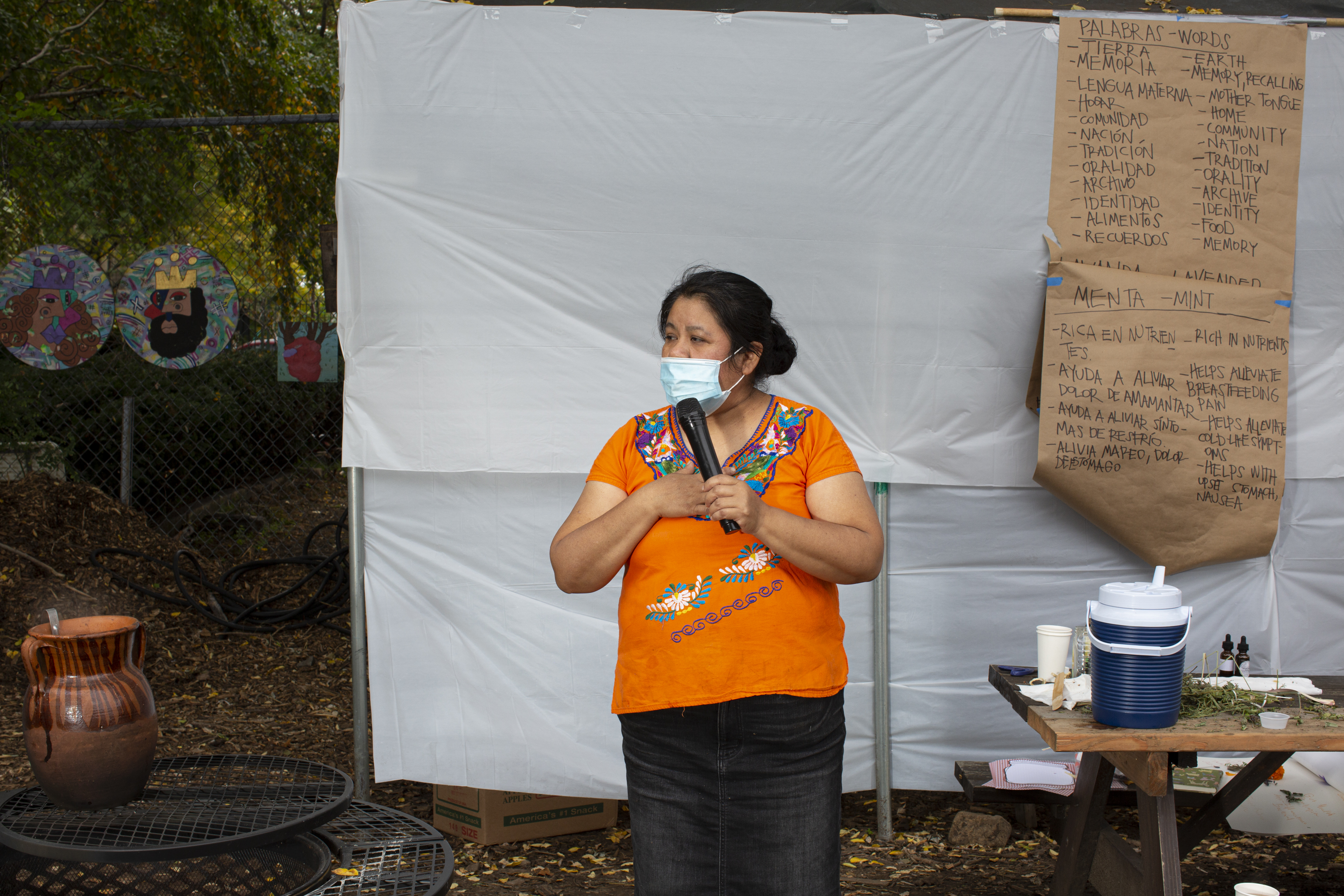 Natalia, wearing an Indigenous Mexican embroidered shirt (orange with flowers), a long black skirt, and a medical mask, shares a memory with the participants of the workshop (out of frame). She uses a microphone to speak, and stands between the table and the fire. In the back, a paper kraft board shows a list of words in English and Spanish that Carolina uses as part of the activity (for instance––tierra/earth; memoria/memory, recalling; lengua materna/mother tongue). Photo by Cinthya Santos-Briones for Brewing Memories workshop, October 24, 2020.