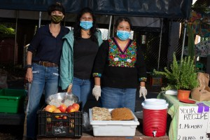 """Angeles, wearing a dark blue shirt and jeans, Carolina, wearing a light green jacket, a black shirt and jeans, and Natalia, wearing an Indigenous Mexican embroidered shirt (Black with flowers) and a long denim skirt, pose for a photo behind a crate full of red apples, a tray with bread and a big red container with hot water. The three of them are wearing masks. On the right side there is a table with a rosemary plant and a poster with instructions that reads """"your recipe"""" """"memory"""" and """"herbs."""" Photo by Cinthya Santos-Briones for Brewing Memories workshop, October 3, 2020."""