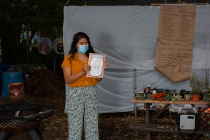 Carolina, wearing an orange shirt and patterned pants, shows a drawing to the participants of the workshop (out of frame). She wears a medical mask. She stands to the right of the table showcasing the different plants participants will learn about during the workshop. On the bench there is a crate with apples and a speaker. In the back, a paper kraft board shows a list of words in English and Spanish that Carolina uses as part of the activity. Photo by Cinthya Santos-Briones for Brewing Memories workshop, October 24, 2020.
