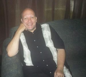 Jim Duke sitting on a couch smiling