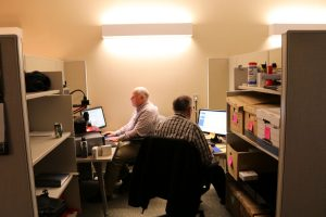 2 men sitting at scanning stations digitizing records