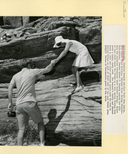 Senator Kennedy helping his wife, Ethel, down a sandstone formation.