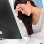 woman at computer suffering from headache