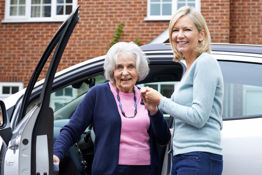 volunteer helping a senior get out of a vehicle to her medical appointment