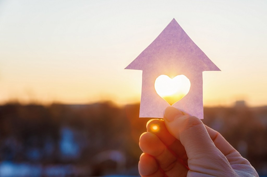 paper house with a carved heart on the background of sunrise