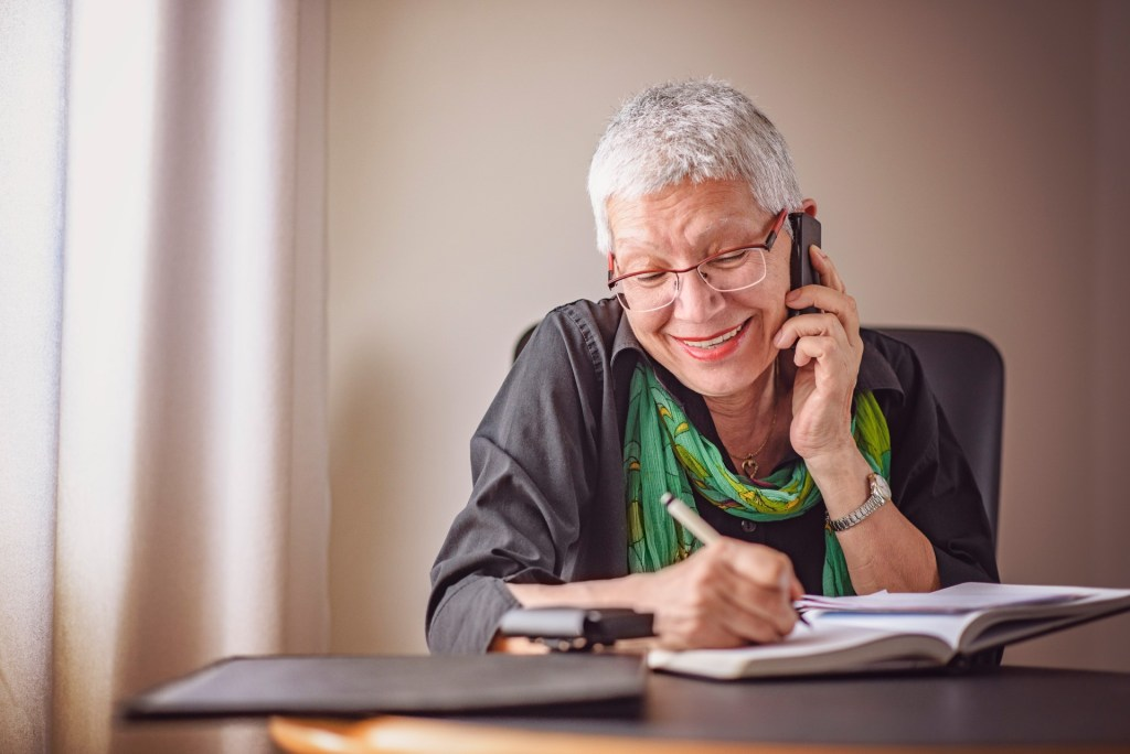 senior getting help with her income taxes over the phone