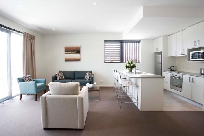 amenager une petite cuisine blanche ouverte sur un salon avec canape gris fauteuil bleu et