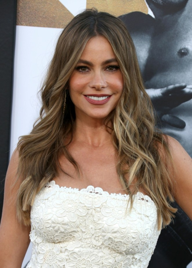 Sofia Vergara with her long hairstyles, blonde highlights, white dress, brown eyes