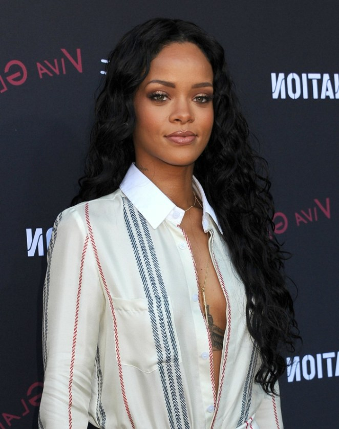 Rihanna with long, black, curly hair, long hairstyles, a white shirt