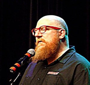 A head and shoulders photo of Rusty, who is bald with red glasses, a full red beard, and a mic on a stand.