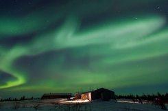 Northern lights (aurora borealis) over Watchee Lodge in northern Manitoba