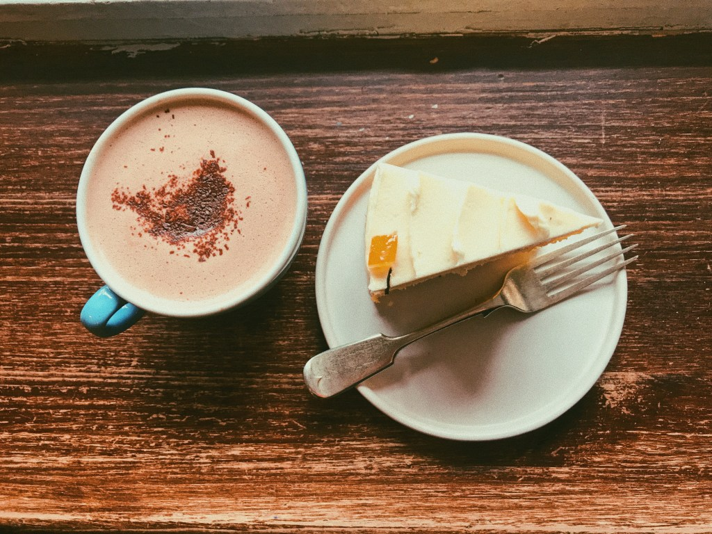 Lovecrumbs cafe flatlay - a cup of hot chocolate and a slice of spiced orange cake.