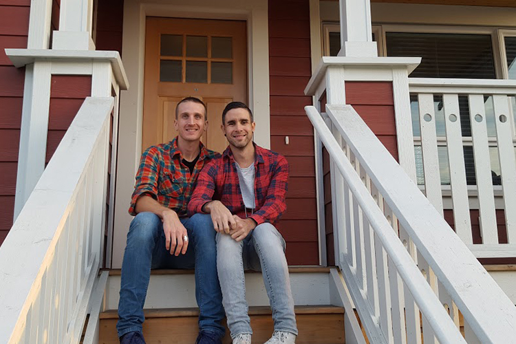 two gay men on the steps of a red townhouse looking happy