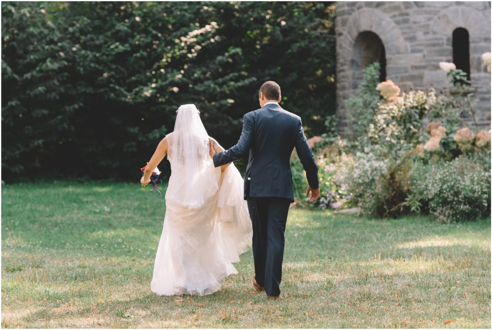Bride and groom walking across a field
